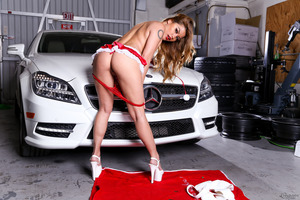 Charmane Star posing in a sexy outfit at a sports car