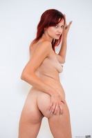 Tattooed redhead Phoenix Askani undresses her black skirt