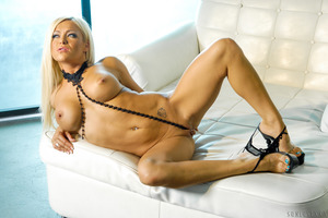 Busty blonde Crista Moore posing alone in her high heels