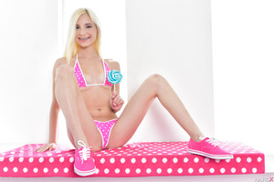 Piper Perri posing in her sweet pink swimsuit with a lolipop